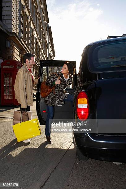 Couple entering London taxi
