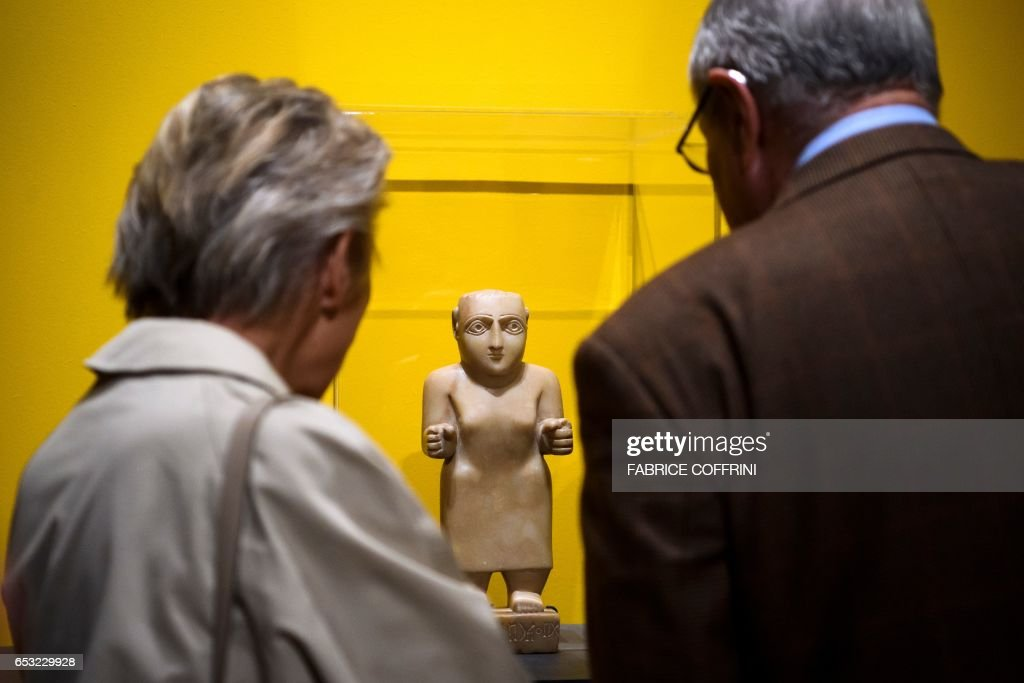 A couple examine a small statue of a standing man from Yemen, discovered during a custom control on April 2013 in the Geneva Freeport warehouse complex, during an exhibition on the illegal trafficking of archaeological objects on March 14, 2017 at the Museum of Art and History in Geneva. Geneva's Museum of Art and History displays for several months nine cultural relics looted from Syria's ancient city of Palmyra, as well as from Libya and Yemen, which were being stored in Geneva's Freeport warehouse complex and seized by the Canton of Geneva. The objects will be on display from March 14 until September 30 of 2017. PHOTO / Fabrice COFFRINI / RESTRICTED