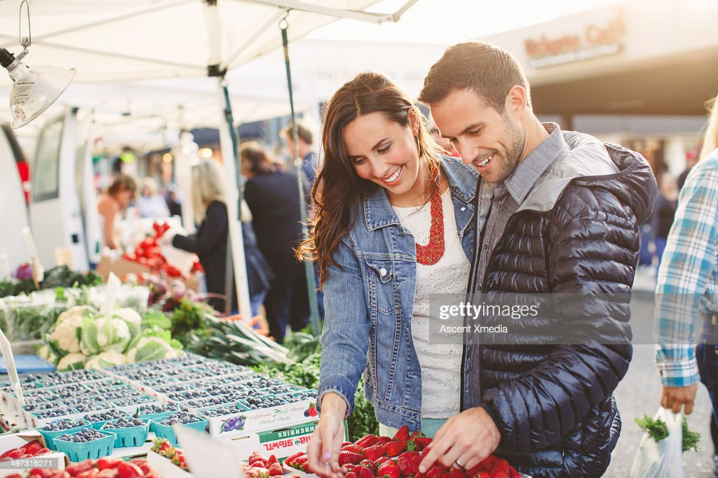 Couple examine fresh fruit in outdoor market