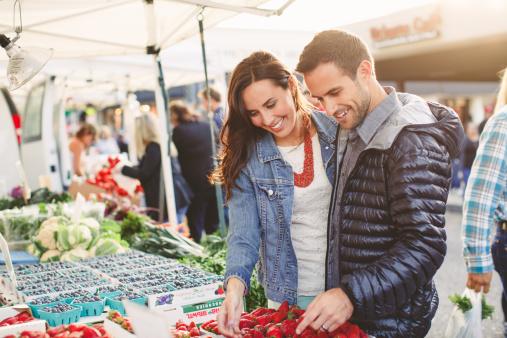 Couple examine fresh fruit in outdoor market
