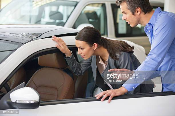 Couple examining a car before buying