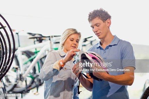 Couple examining bicycle helmet in shop : Foto de stock