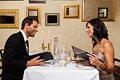 Couple examining menus in restaurant