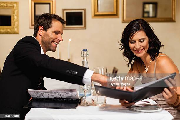 Couple examining menus in restaurant
