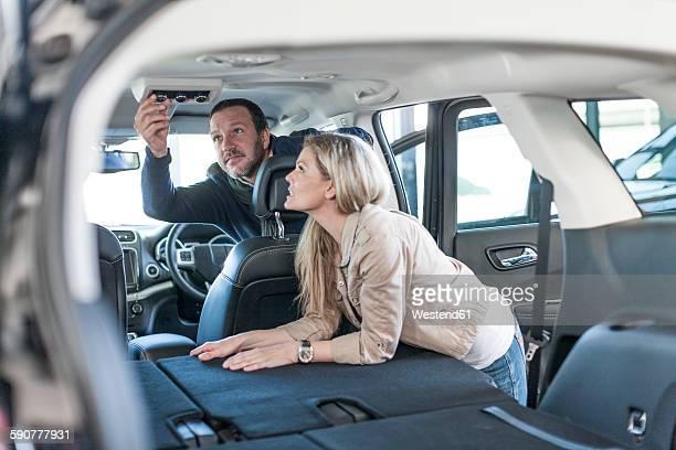 Couple examining new car at car dealership