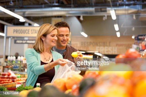 Couple examining produce in supermarket : Foto stock