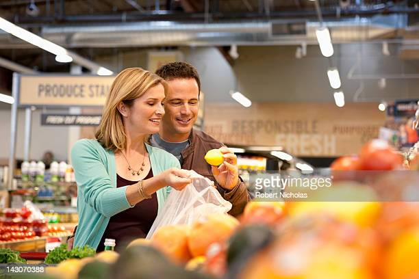 Couple examining produce in supermarket