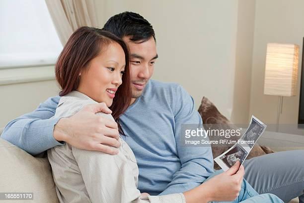 Couple examining sonogram on sofa