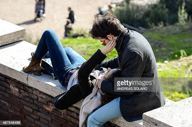 A couple exchange tendernesses in front of Ancient Foro Romano in central Rome on February 7 2014 AFP PHOTO / ANDREAS SOLARO