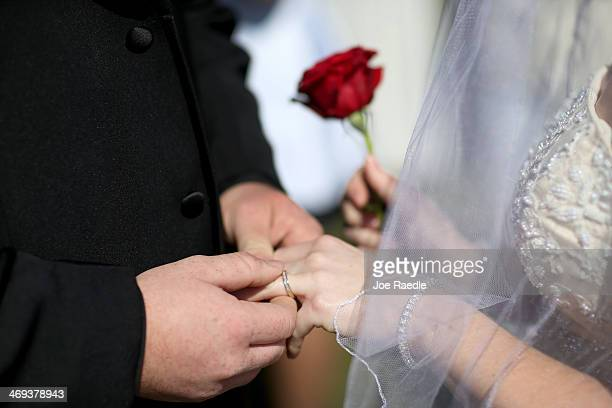 A couple exchanges rings as they are wed during a group Valentine's day wedding at the National Croquet Center on February 14 2014 in West Palm Beach...