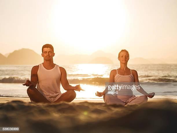Couple exercising Yoga at sunset.