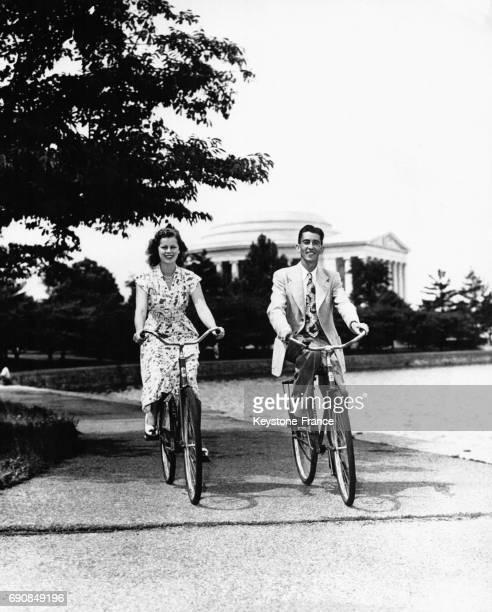 Couple faisant du vélo le long du Potomac au fond on voit le Jefferson Memorial à Washington DC EtatsUnis