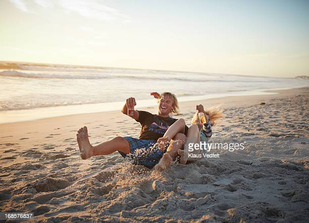 Couple falling in the sand in the sunset