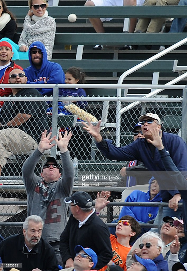 A couple fans try to make a play on a foul ball during a game between the Chicago Cubs and the San Francisco Giants at HoHoKam Park on February 24, 2013 in Mesa, Arizona.