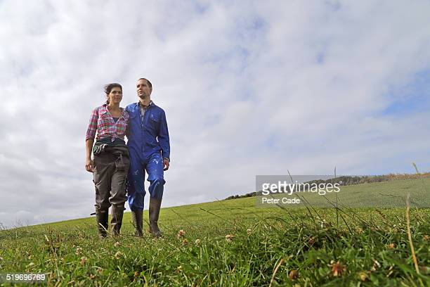 Couple , farmers walking through field