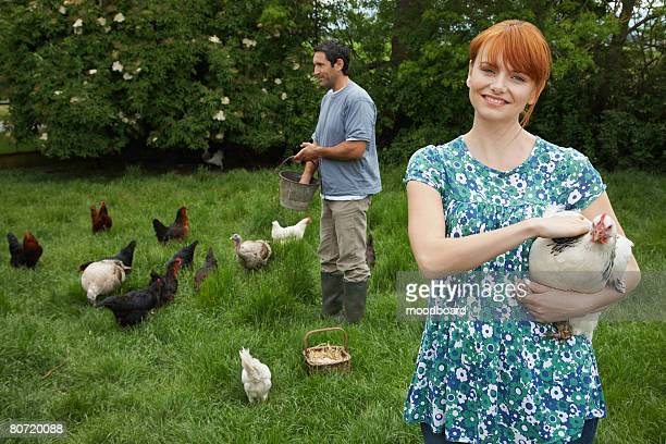 Couple Feeding Chickens
