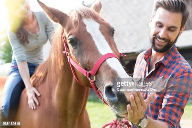 Couple feeding horse