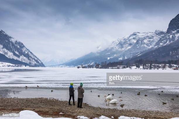 A couple feeds the birds at frozen Traunsee (Lake Traun); Austria