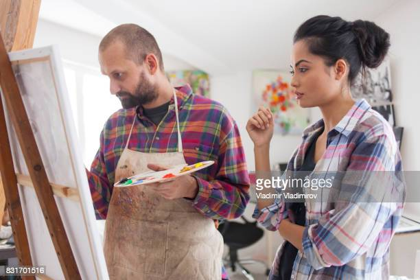 Couple fine artists drawing in studio