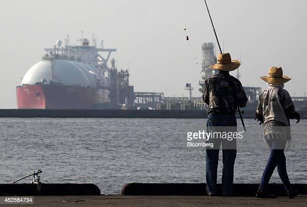 A couple fishes in front of a liquefied natural gas tanker berthed at Tokyo Electric Power Co's Futtsu gasfired thermal power plant in Futtsu Chiba...
