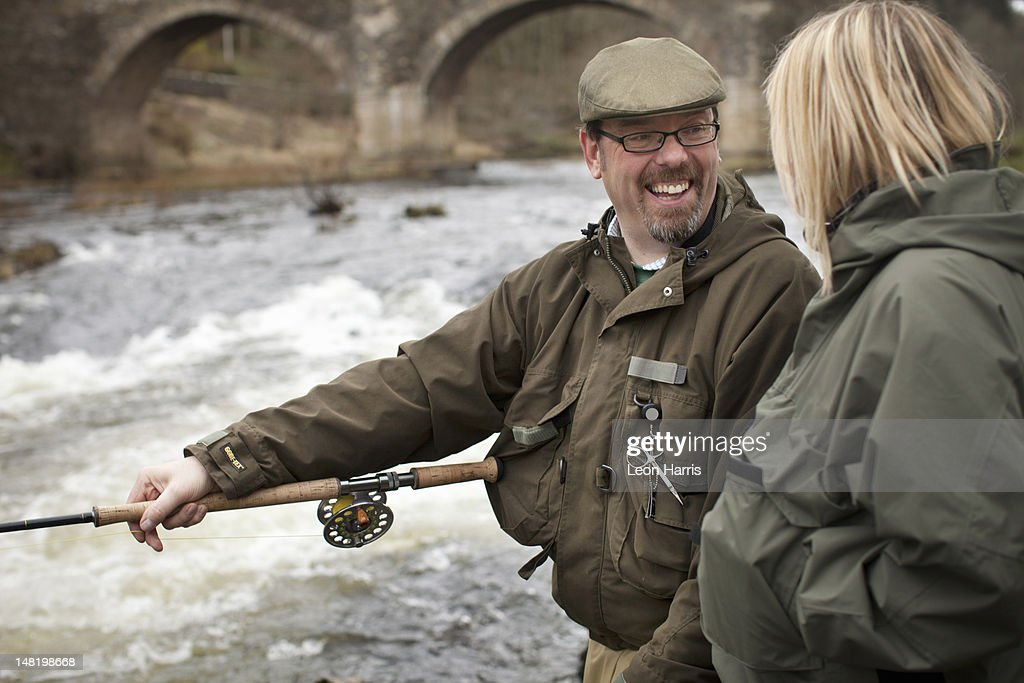 Couple fishing for salmon in river : Stock Photo