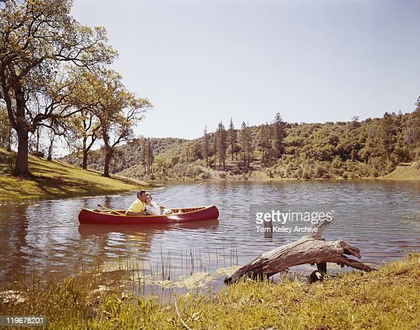 Par pesca desde canoa en el lago
