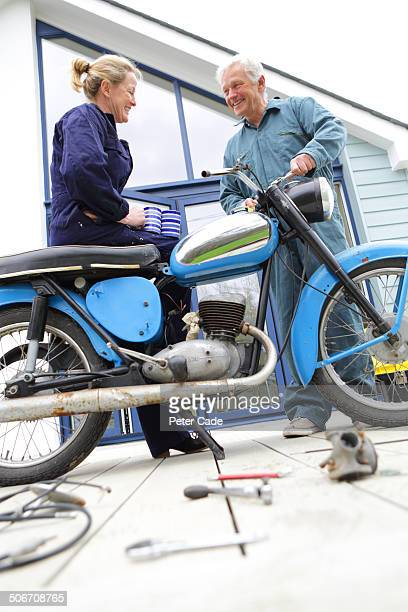 couple fixing motor bike, laughing