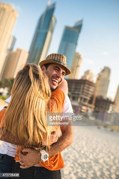 couple flirting against the skyline of dubai marina