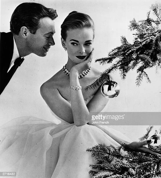 A couple flirting beside a Christmas tree December 1955 The female model is Susan Abraham Original Publication Housewife Magazine pub 1955