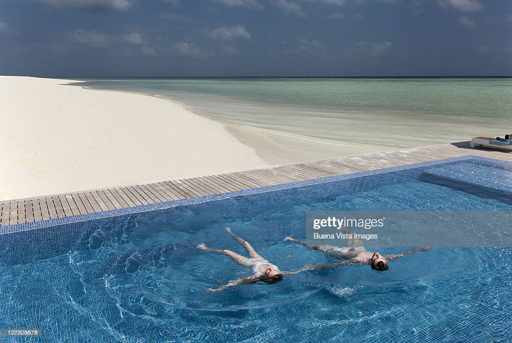 Couple floating in infinity pool on beach : Stock Photo