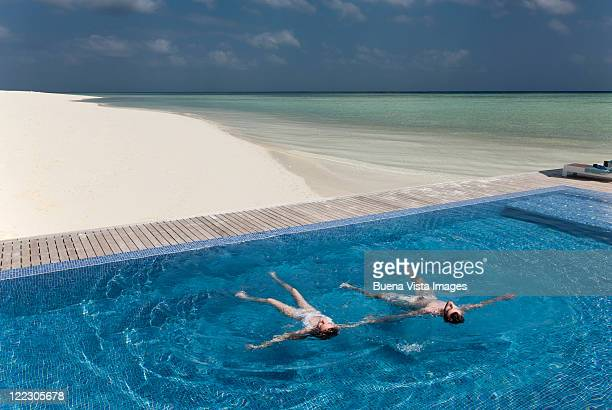 Couple floating in infinity pool on beach