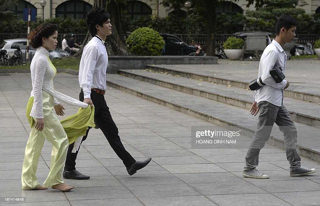 A couple follow a photographer at a public park looking for different locations for their wedding shoot in downtown Hanoi on April 24, 2013. AFP PHOTO/HOANG DINH Nam