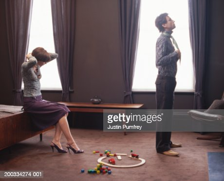 couple getting dressed in bedroom toys on floor stock photo