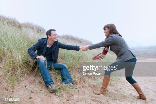 Couple getting up from sand dune