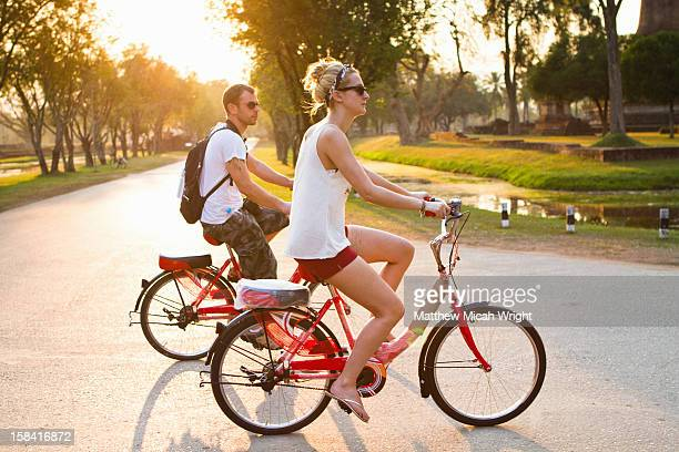 A couple goes bike riding at sunset