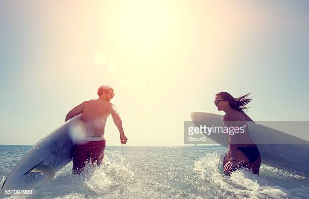 Couple going surfing at sunset.