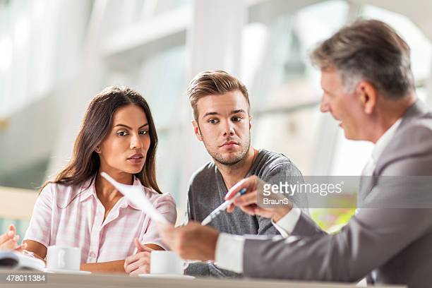 Couple going through paperwork with their real estate agent.