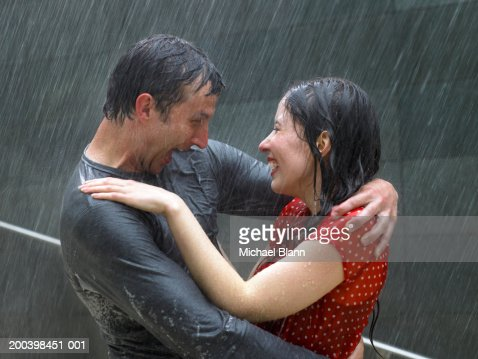 Couple greeting each other in rain, side view, close-up : Stock Photo