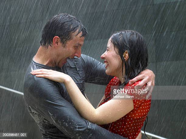 Couple greeting each other in rain, side view, close-up