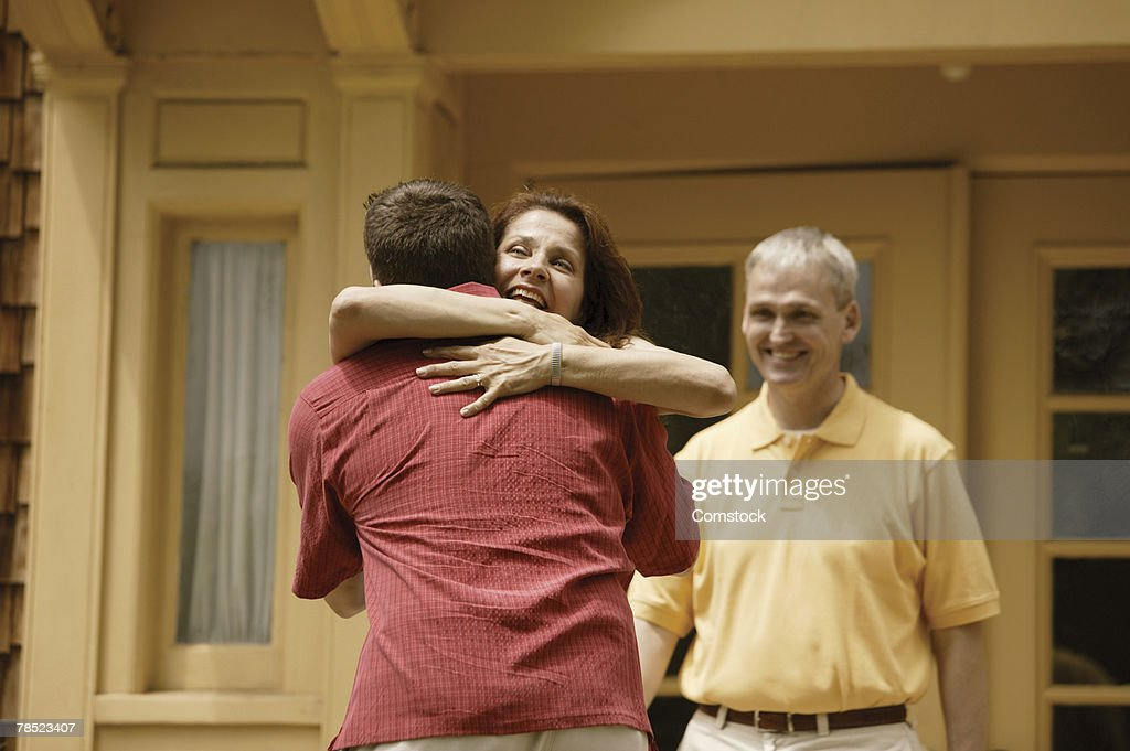 Couple greeting son returning home