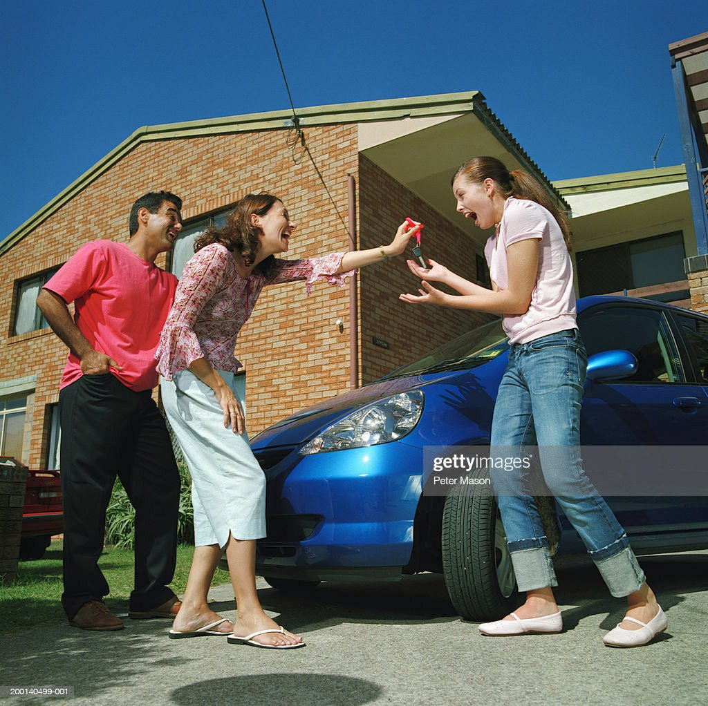 Couple handing car keys to teenage daughter (15-17), smiling : Stock Photo