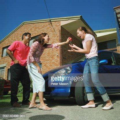 Couple handing car keys to teenage daughter (15-17), smiling : Foto de stock