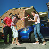 Couple handing car keys to teenage daughter (15-17), smiling