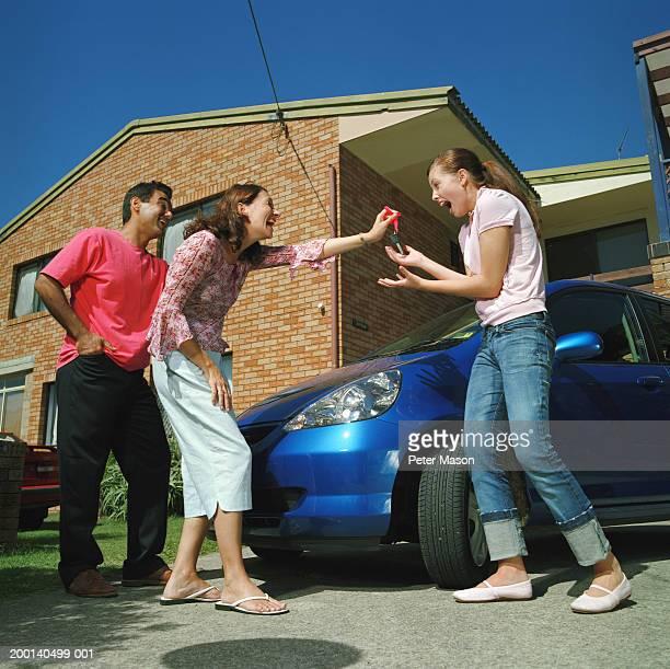 Couple handing car keys to teenage daughter (15-17), smiling