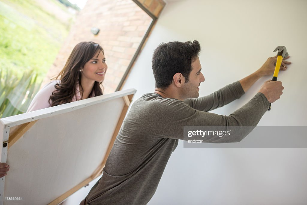 Couple hanging a painting : Stock Photo