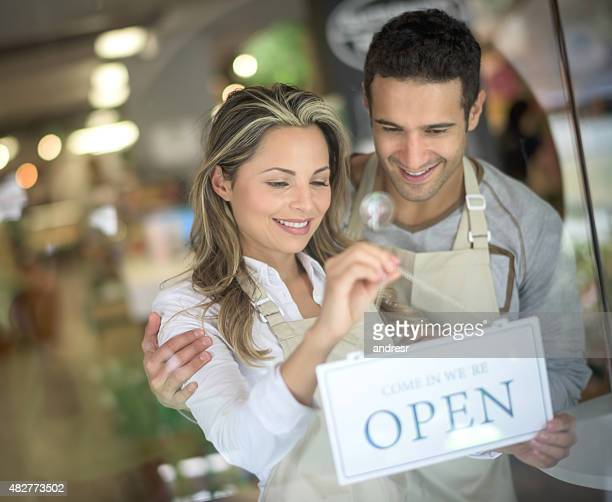 Couple hanging an open sign at a business