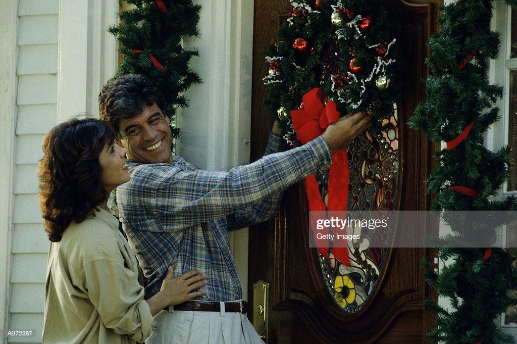 Couple hanging Christmas wreath on door : Stock Photo