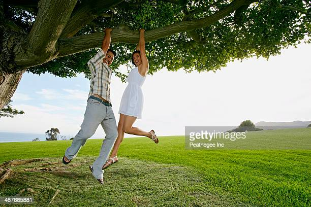 Couple hanging from tree branch in field