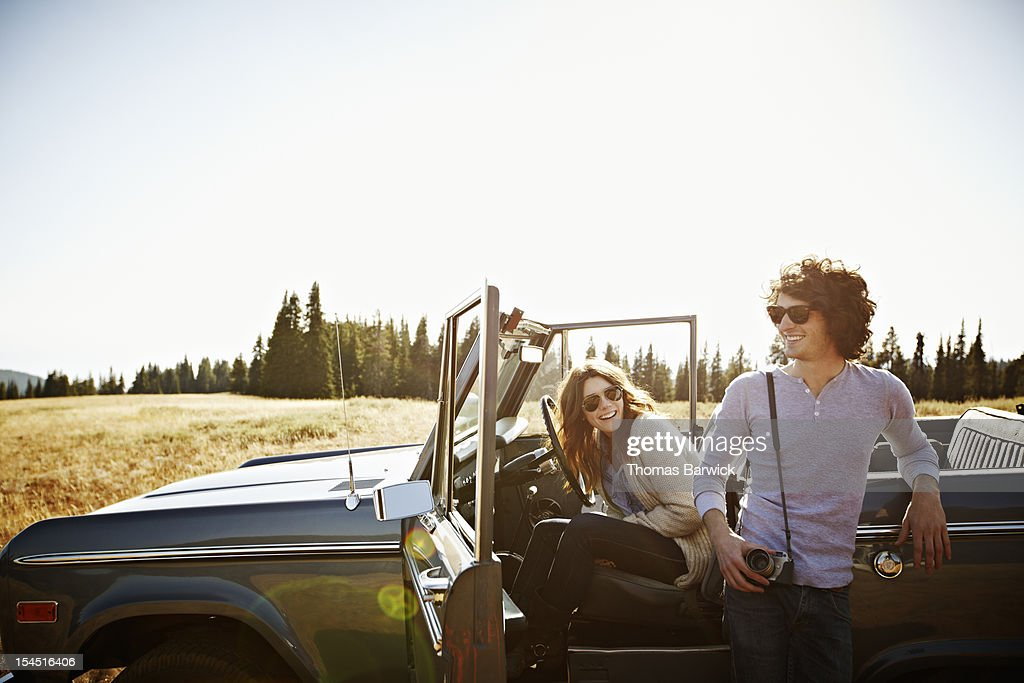 Couple hanging out in convertible in field : Stock Photo
