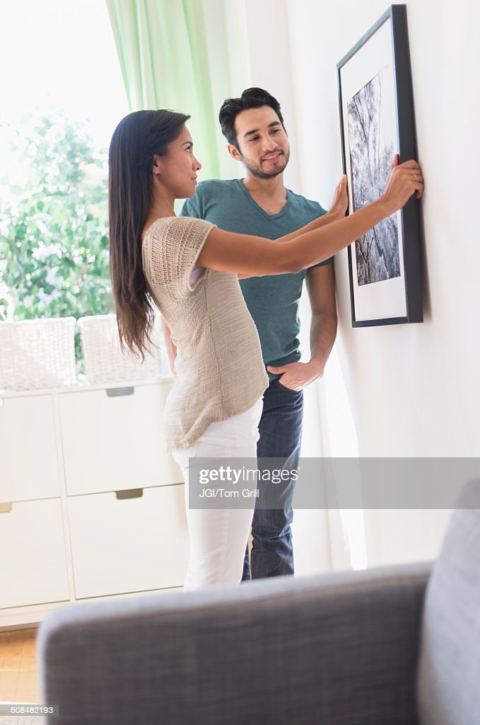 Couple hanging picture together